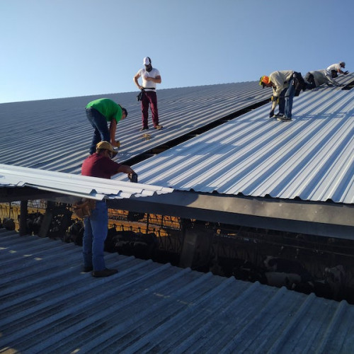 men installing white metal roofing